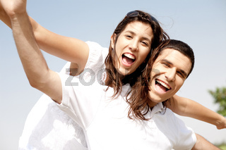 Smiling young couple holding hands eachother while piggyback