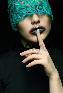 Halloween beauty portrait of young beautiful woman with green lacy ribbon on eyes on black