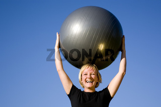 Frau mit Ball macht Sport Übungen