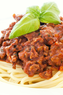 Spaghetti with bolognese sauce and basil as closeup in a white plate