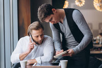 Two businessmen discussing work and using tablet