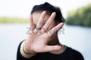 woman hiding face behind hand