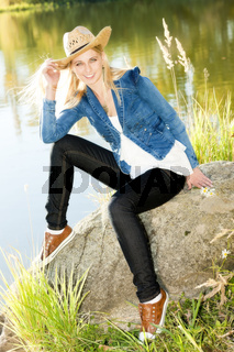 young woman sitting on stone at pond