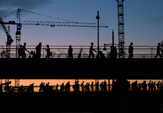 silhouettes of people crossing bridge with sunset sky background