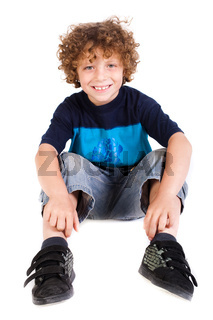Adorable young kid sitting on floor