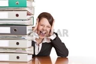 Frustrierte Frau schreit im Büro hinter Ordnerstapel