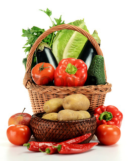Wicker basket and vegetables on white