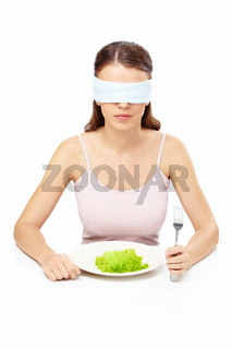 Girl blindfold sits before plate with salad leaf