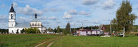 Typical rustic Russian landscape - a church next to fields, road and sheds