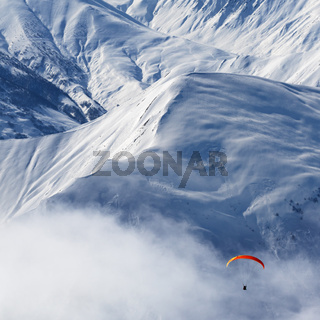 Paragliding at snowy mountains in haze