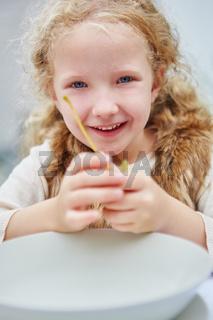Mädchen sitzt lächelnd vor einem Teller