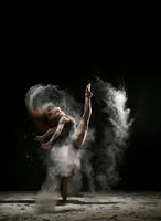 Sexy girl in a cloud of white dust studio portrait