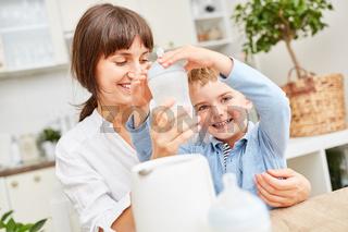 Junge hilft beim Erwärmen von Muttermilch