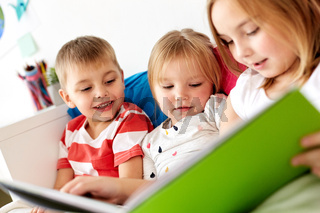 little kids reading book in bed at home