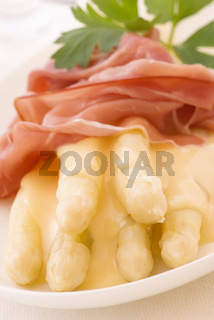 White and green asparagus with gammon and sauce as closeup on a white plate