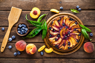 Peach cheese cake or pie with fresh blueberry on wooden rustic background, top view, closeup