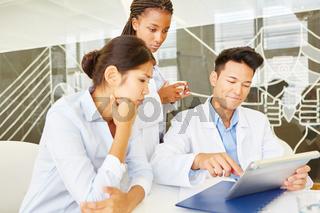 Ärzte arbeiten zusammen am Tablet PC