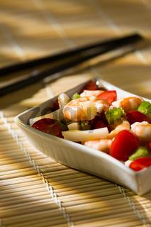 Shrimp salad on a bamboo tablecloth and chopsticks