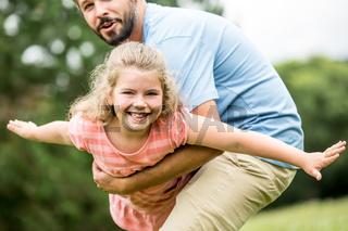 Mädchen fliegt in den Armen des Vaters
