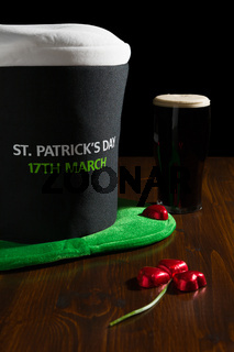 St Patrick day with a pint of black beer, hat and shamrock over a table