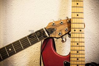 Closeup of two guitar necks over wall background