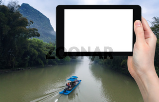 tourist photograps boat on river in Yangshuo