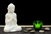 White figure in meditation pose with pebbles and candle