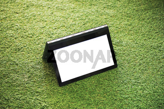 Laptop with blank white screen on the green grass