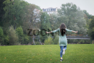 Young woman running in the rain