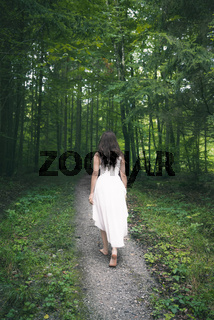 Woman in a white dress walking through a forest