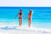 Girls running to sea