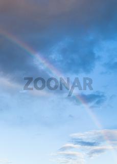 rainbow between dark clouds in blue evening sky