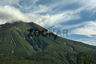Tourist helicopter against the backdrop of volcano Priemysh. South Kamchatka Nature Park.