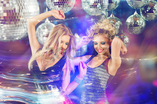 Two young women dancing at night disco club