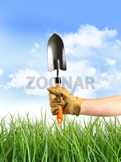 Hand holding garden trowel against blue sky