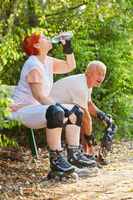 Senioren Paar als Inline Skater trinkt Wasser