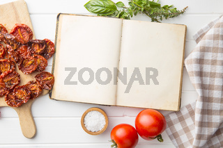 Old recipe book with tomatoes, herbs and salt.