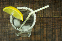 A glass of water with ice and lemon, flat view.