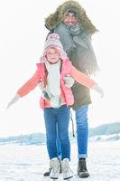 Vater hilft Tochter beim Schlittschuh laufen lernen