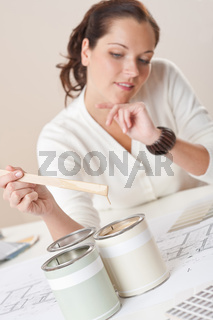 Female interior designer with cans of paint at office