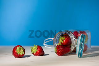 Strawberries and a glass jar full of strawberries lying down on a table