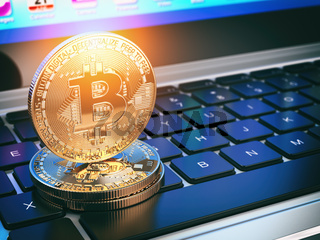 Golden bitcoins on laptop keyboard. Mining of cryptocurrency.