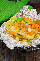 Pike with leeks and carrots in foil on board