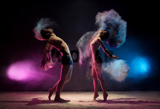 Young couple poses in color dust cloud studio shot