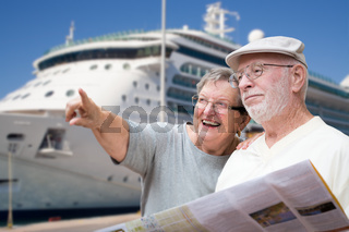 Happy Senior Adult Couple Tourists with Brochure Next To Passenger Cruise Ship.