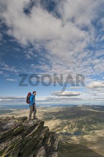 Wanderer auf einem Gipfel im Alvdal Vestfjell, in der Ferne der Berg Rendalssoelen, Rendalen, Hedmark, Norwegen