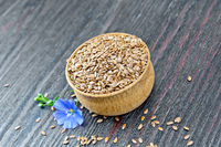 Flaxen brown seed in bowl with flower on board