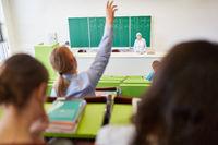 Student meldet sich und hebt die Hand