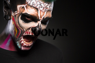Monster makeup, man with zombie face, studio portrait.
