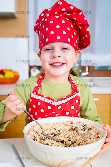 Girl preparing granola in the kitchen at home